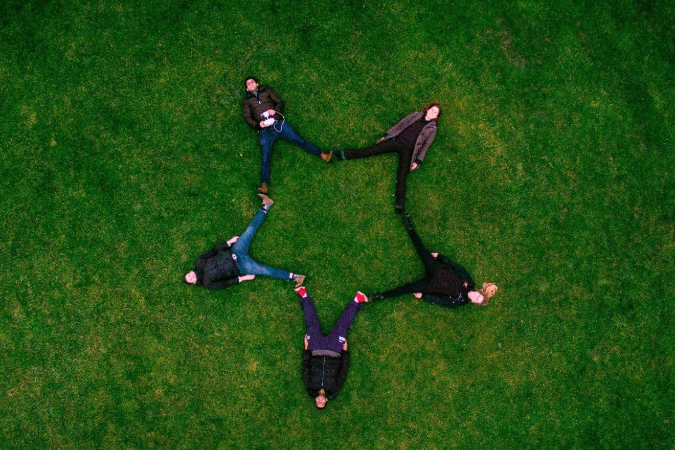 sidharth-bhatia-vijf mensen in stervorm in gras-unsplash
